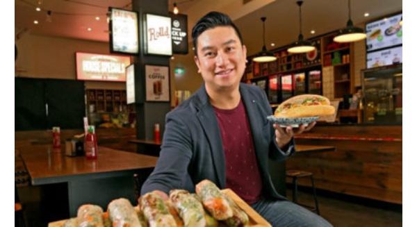 Ông Bao Hoang- đồng sáng lập thương hiệu thức ăn Việt mang tên Rolld- giới thiệu món bánh mì và nem cuốn. (ảnh: afr.com).