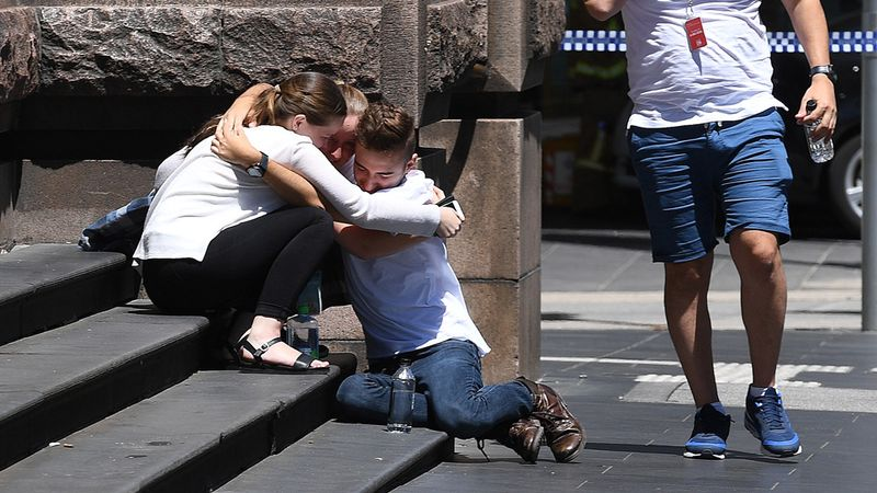 People are seen hugging on the corner of Bourke and Elizabeth street